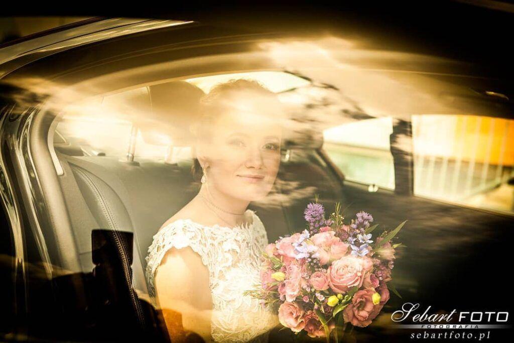 fotografia slubna panna młoda w samochodzie